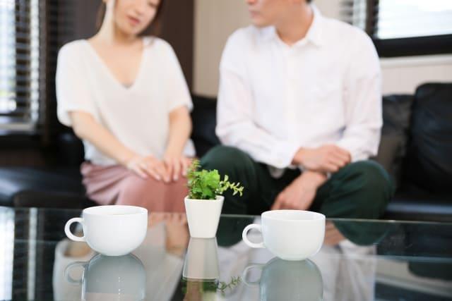 男女がコーヒーを飲みながら相談している画像