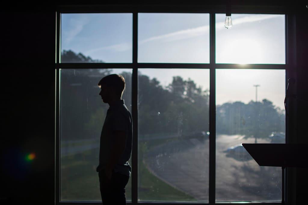 男性が窓ごしに結婚を悩んでいる画像